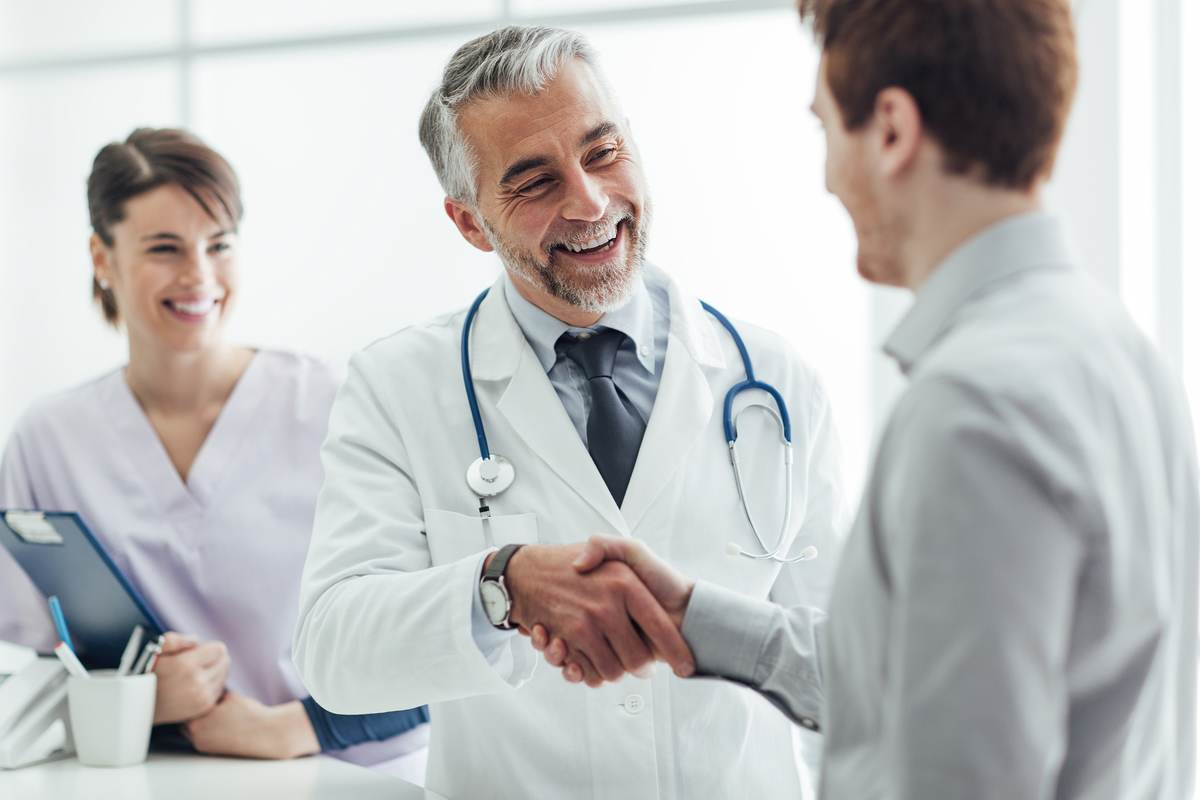 A senior doctor shaking hands with a young man