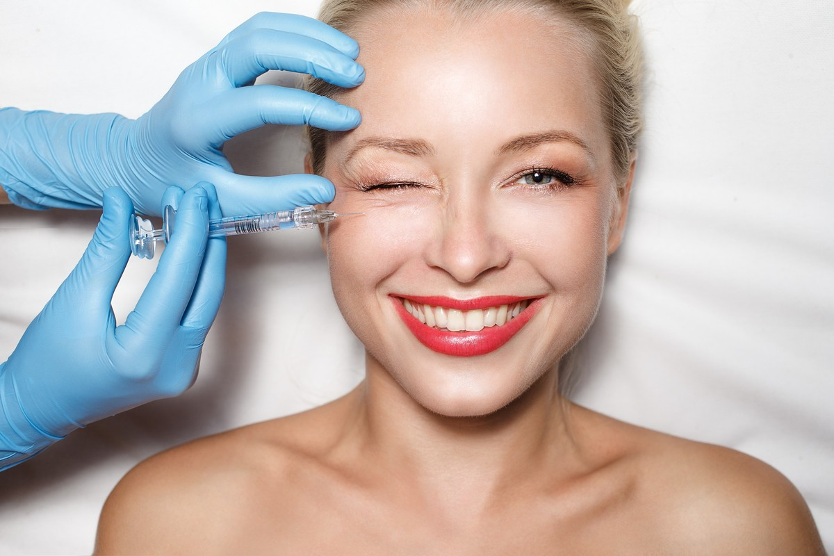 A woman happily receiving a Botox injection in her right cheek